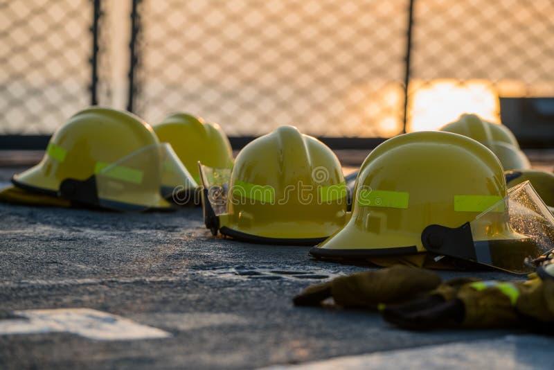 Hjälmar för brandstridighet torkar på däcket för marinskeppet efter bruk Säkerhetsnät har sett som en bakgrund orange himmel mell fotografering för bildbyråer