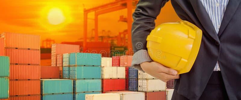 Hjälmen för personinnehavguling för arbetarsäkerhet på industriell portbakgrund och ljus skiner solnedgång arkivbilder