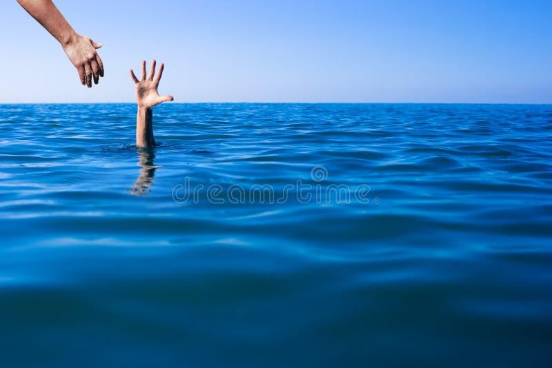 Hjälp att räcka för att drunkna manlivbesparingen i havet eller havet royaltyfria bilder