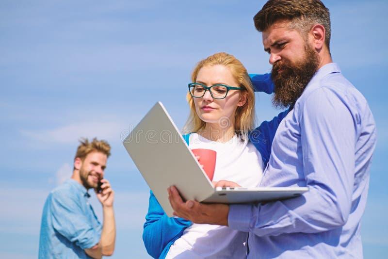 Hjälp för ny luft som förnyar mening Utomhus- solig dag för kollegabärbar datorarbete, himmelbakgrund Vänner tycker om ny luft oc arkivfoton
