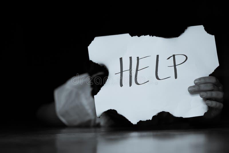 HJ?LP kvinna med hj?lptecknet Flicka som rymmer ett papper med inskriften flicka i tillf?llig kl?der som rymmer arket av papper royaltyfri fotografi