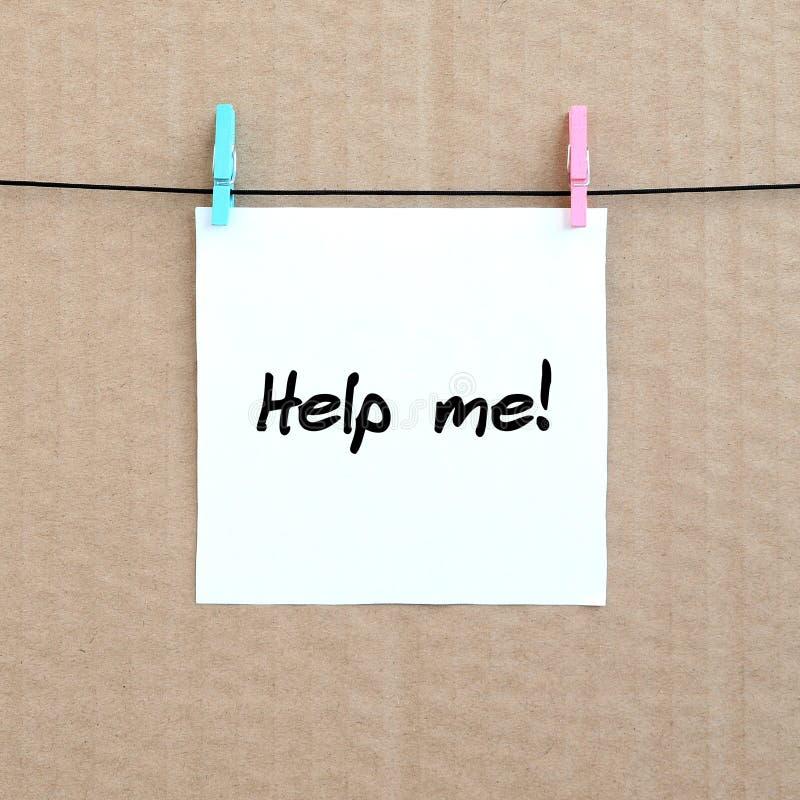 Hjälp mig! Anmärkningen är skriftlig på en den vit klistermärke hängningar med en cl fotografering för bildbyråer