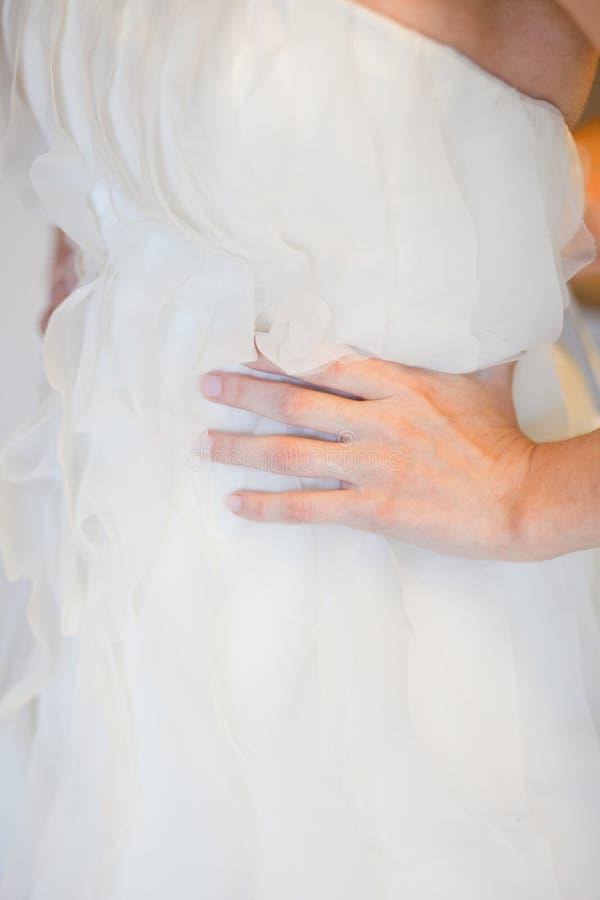 Hjälpa bruden att sätta på hennes bröllopsklänning arkivfoto