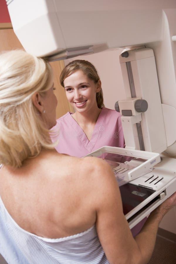 hjälpa patient genomgå för mammogramsjuksköterska royaltyfri fotografi