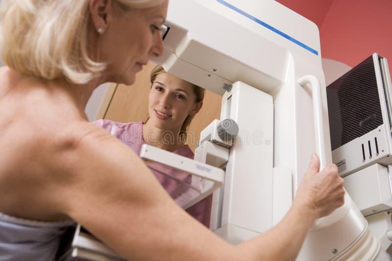 hjälpa patient genomgå för mammogramsjuksköterska royaltyfri foto