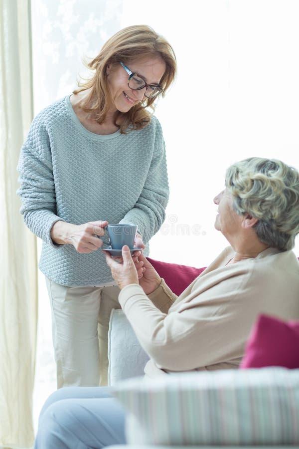 Hjälpande äldre kvinna för vårdare arkivbild