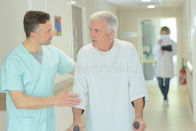 Hjälpande äldre patient för manlig doktor med kryckor arkivbild