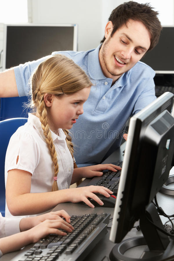 Hjälpande flicka för lärare som använder datoren i grupp arkivfoto
