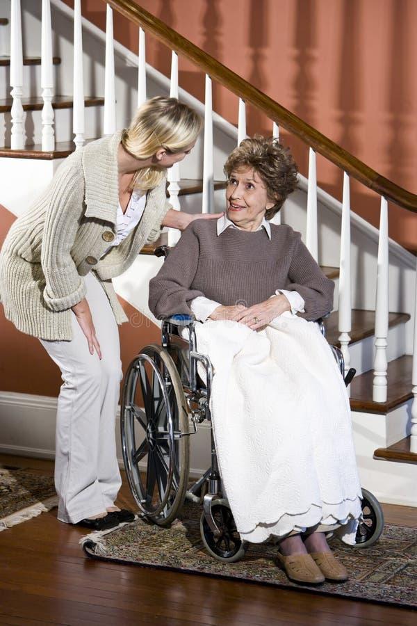 hjälpande hög rullstolkvinna för sjuksköterska royaltyfria bilder