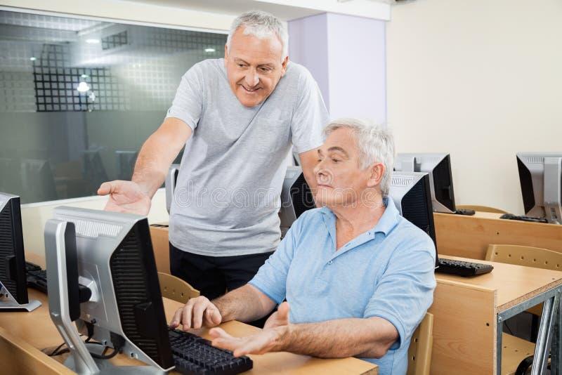 Hjälpande manlig klasskompis för hög man, i att använda datoren royaltyfri foto