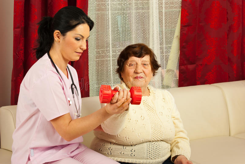 Hjälpande pensionär för terapeut som gör övningar royaltyfri fotografi