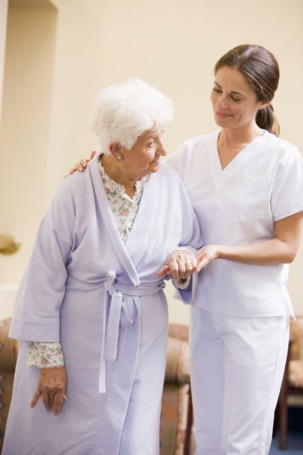 hjälpande sjuksköterskapensionär som går kvinnan royaltyfri fotografi
