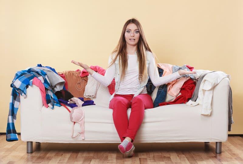 Hjälplöst kvinnasammanträde på soffan i smutsigt rumhem royaltyfria foton