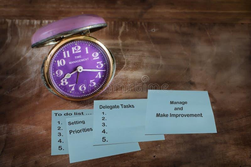 Hjälpmedel av tidledning på klibbig anmärkning med klockan royaltyfri bild