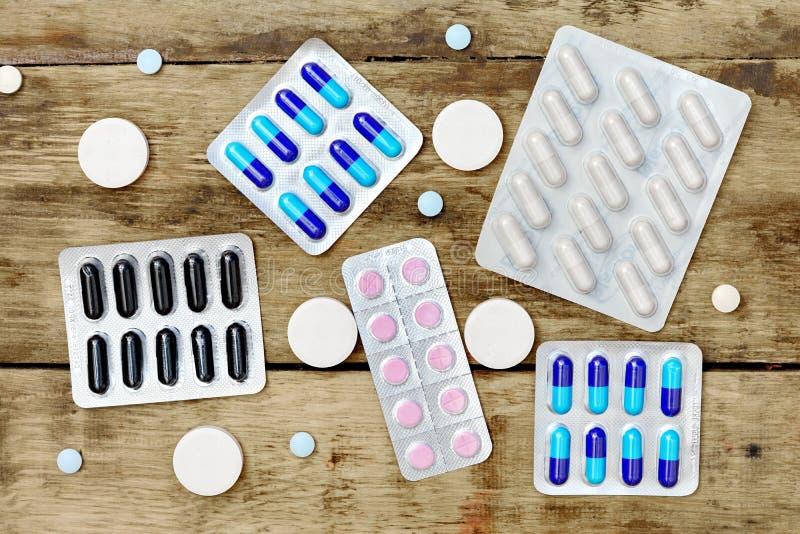 hjälpmedel för apotek för bakgrundsläkarbehandlingmedicin set Preventivpillerar på en trätabell Medicin arkivfoto