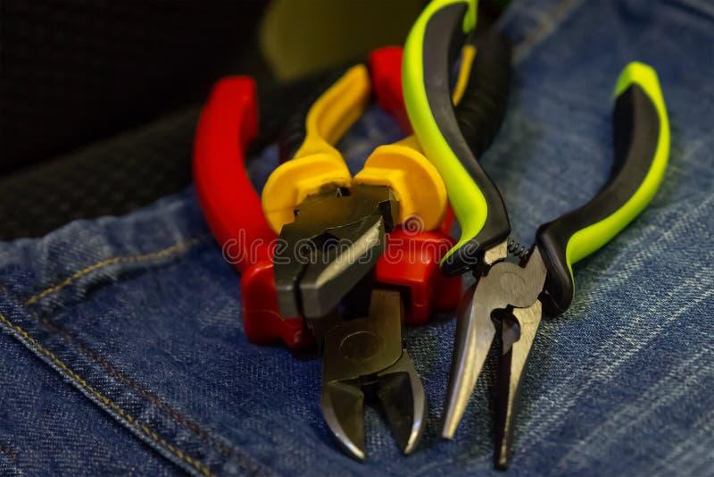 Hjälpmedel för färgrik penna för pojkar för uppsättning för Grungestilbakgrund reparerar röda gröna elektrisk utrustning på jeans royaltyfria bilder