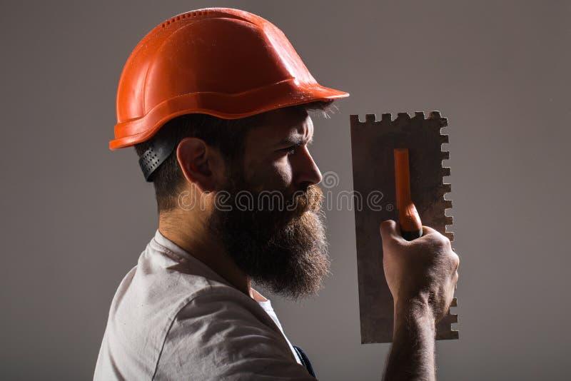 Hjälpmedel murslev, faktotum, manbyggmästare Murarehjälpmedel, byggmästare Byggmästare i den hårda hatten, hjälm Skäggig manarbet arkivbilder