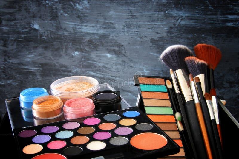hjälpmedel och borstar för makeupskönhetsmedelskönhet i framdel av svart träbakgrund royaltyfria foton