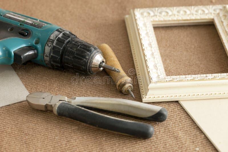 Hjälpmedelenhetsramar, ramar, för målningar, fotografier, skruvmejseln, trådskärare, plattång ritar på beige bakgrund arkivbilder