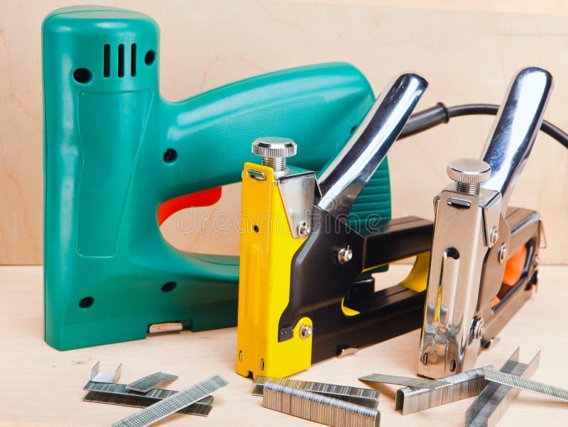 Hjälpmedlet - elektriska häftapparater och manuellt mekaniskt - för reparationsarbete i huset royaltyfri fotografi