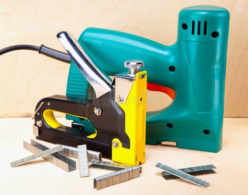 Hjälpmedlet - elektriska häftapparater och manuellt mekaniskt. Stilleben royaltyfri fotografi