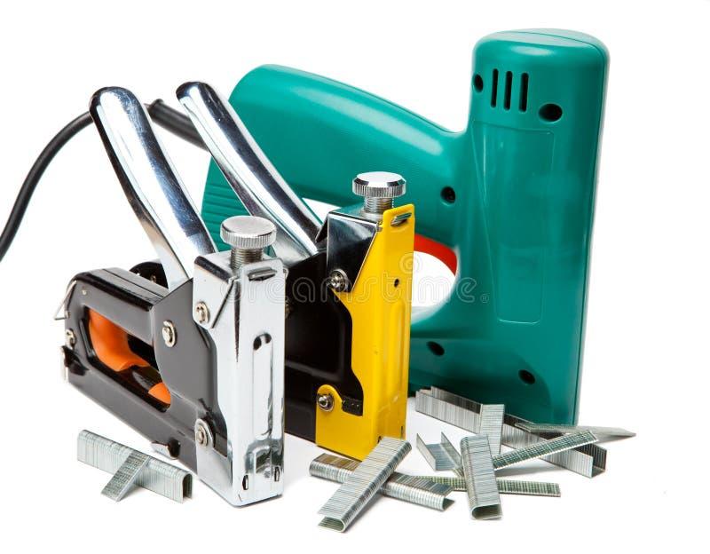 Hjälpmedlet - elektriska häftapparater och manuellt mekaniskt. Stilleben på a arkivfoto