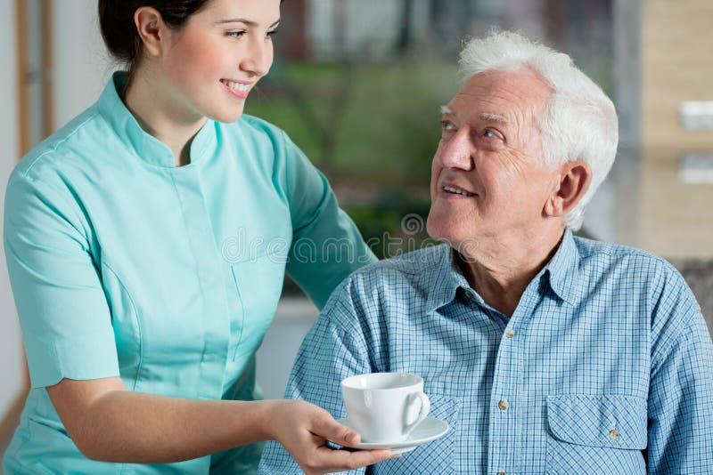 Hjälpreda som ger koppen kaffe royaltyfria bilder