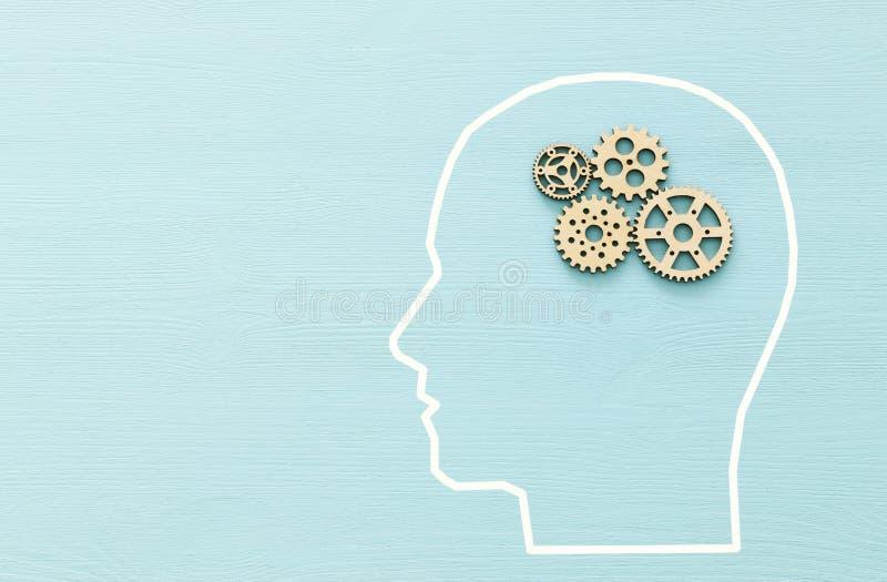 Hjärnbeställning som göras från träkugghjul in i det mänskliga huvudet Begrepp av att tänka, workflowen, adhd och att lära arkivfoton