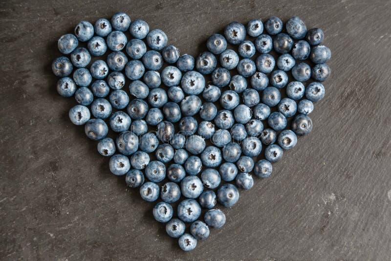 Hjärta av blåbär kritiserar på plattan royaltyfri fotografi