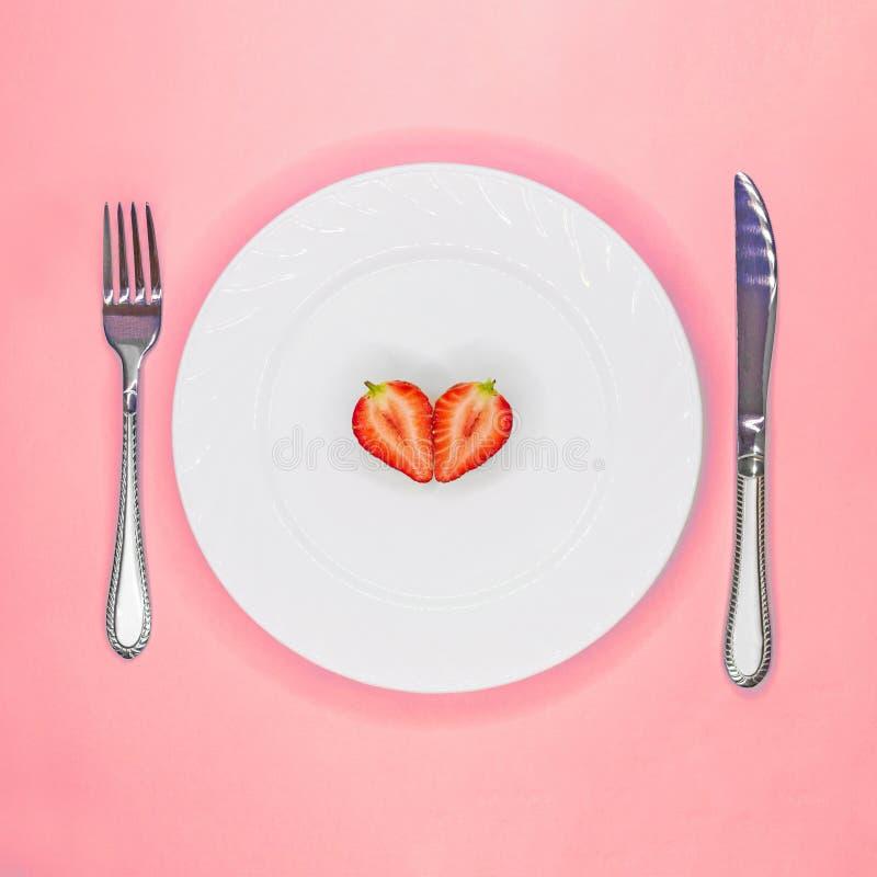 Hjärta av jordgubbehalvor på den vita plattan L?gt - kalorin bantar begrepp Vegeterian råkost isolerat p? vit som ?r selektiv fok arkivbild
