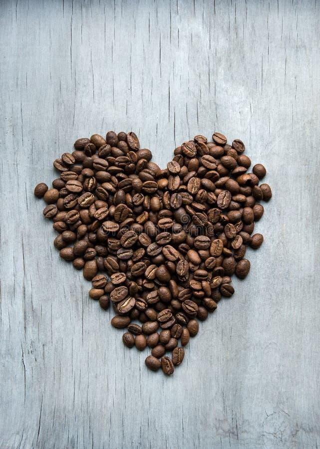 Hjärta av kaffebönor på träbakgrunden royaltyfri bild