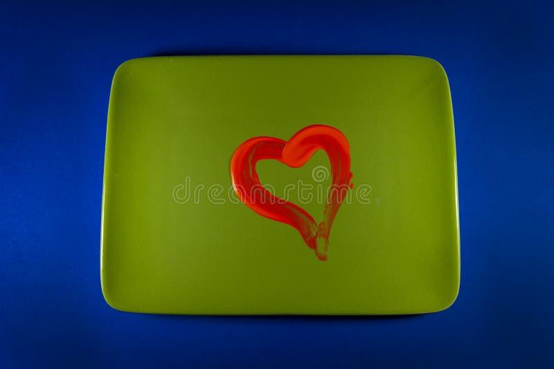 Hjärta av röd tomatsås på en grön platta royaltyfri foto