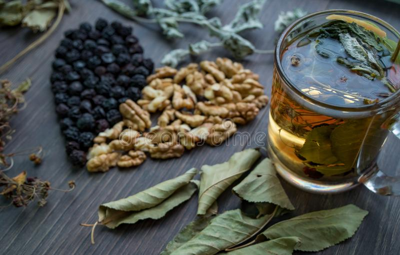 Hjärta av torkade körsbär, muttrar och torkade sidor av te, sidosikt arkivbild