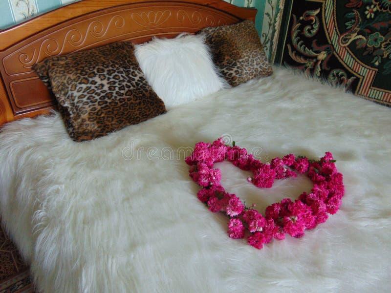 `-Hjärta`en av rosor på sängen royaltyfria bilder