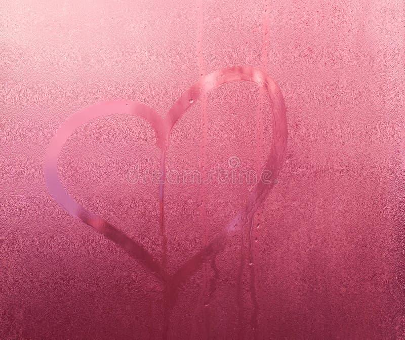 Hjärta förälskelsesymbol på svettigt exponeringsglas, rosa lutningbakgrund arkivbild