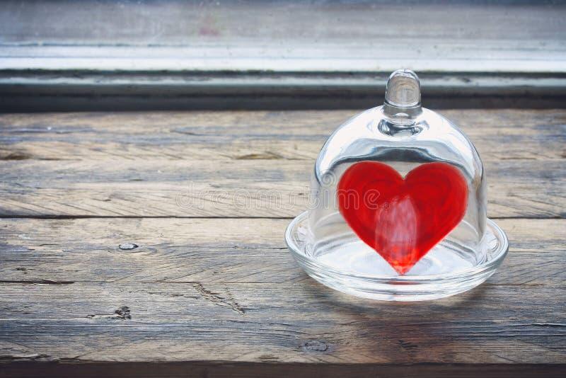 Hjärta för dag för valentin` s i en glass krus under ett lock royaltyfria bilder