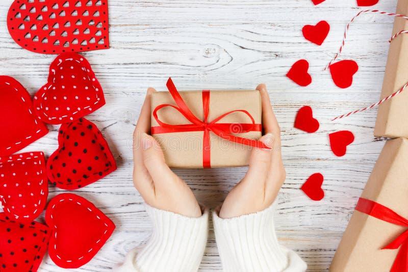 Hjärta för två rosa färg Flickahanden ger valentingåvaasken med en röd hjärta inom på en vit gammal trätabell vektor för valentin royaltyfri bild