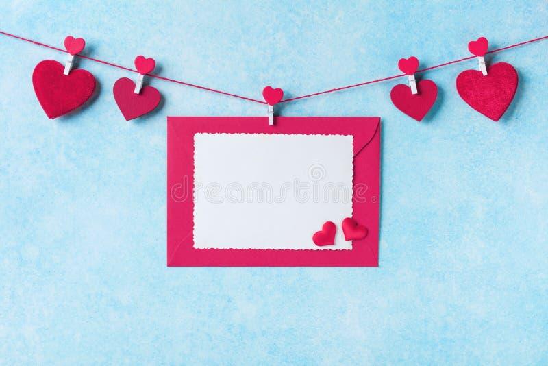 Hjärta för två rosa färg Girland av röda hjärtor på klädnypor och kuvertet med kortet på den blåa väggen arkivbilder
