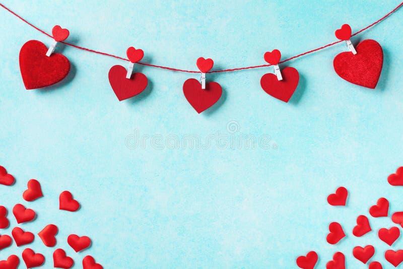 Hjärta för två rosa färg Girland av röda hjärtor på klädnypor på turkosväggen royaltyfri fotografi