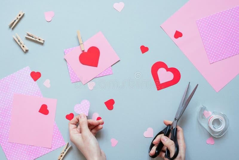 Hjärta för två rosa färg Händer som gör valentinkortet med hjärta och på den blåa bakgrunden fotografering för bildbyråer