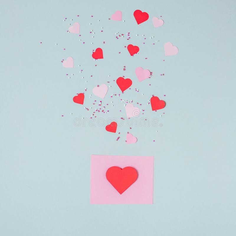 Hjärta för två rosa färg Valentinkort med pappers- hjärtor på den blåa bakgrunden arkivfoto