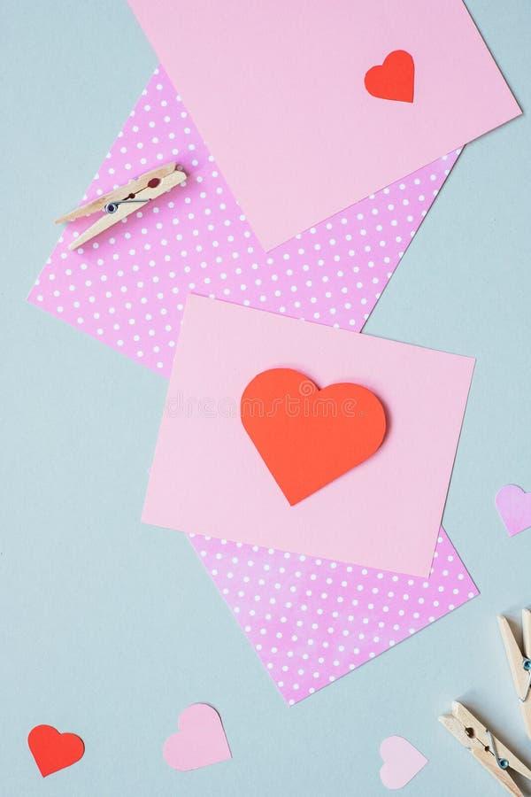 Hjärta för två rosa färg Valentinkortet med hjärta och hantverket skyler över brister på den blåa bakgrunden royaltyfri fotografi