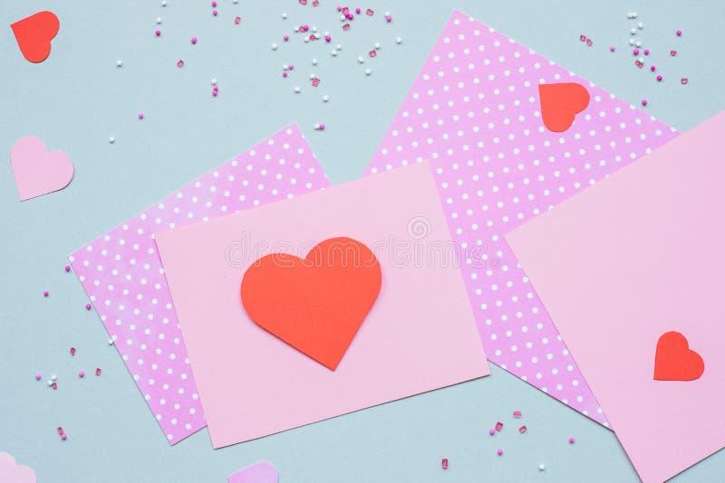Hjärta för två rosa färg Valentinkortet med hjärta och hantverket skyler över brister på den blåa bakgrunden arkivbild