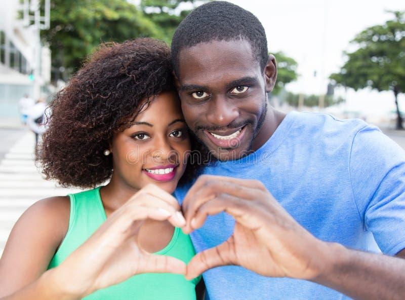 Hjärta för visning för afrikansk amerikanförälskelsepar royaltyfri foto