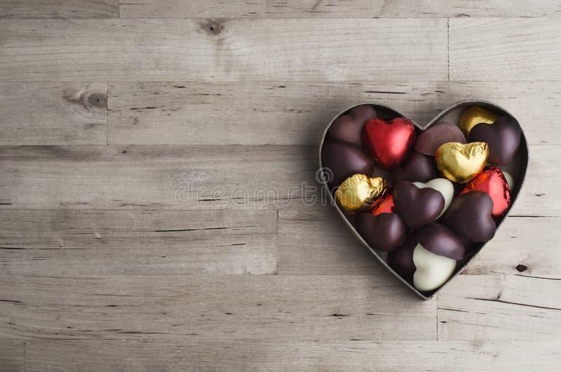 Hjärta formad ask av hem- gjorda choklader på trä arkivbilder