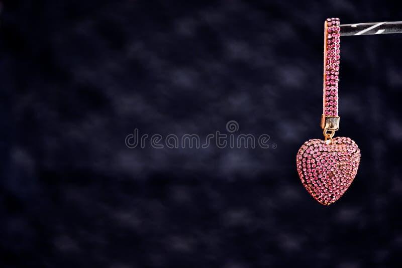 Hjärta-formad gåvafärg i ros-guld på en svart bakgrundsshini arkivbilder