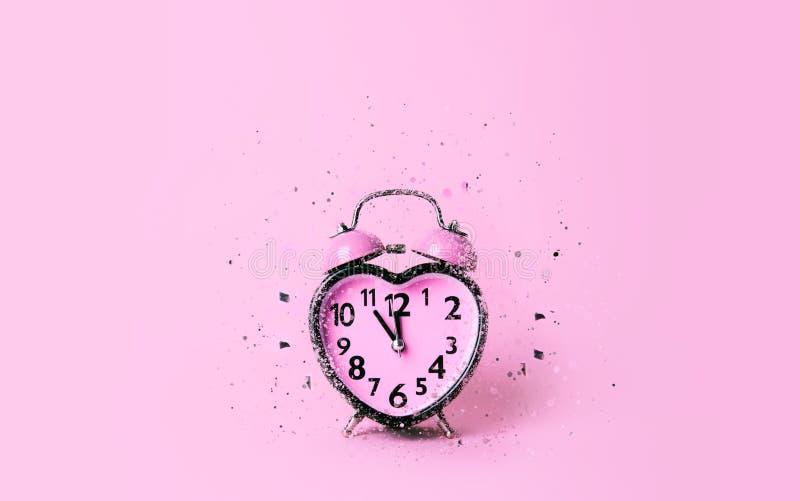 Hjärta formad klocka på rosa bakgrund arkivfoto