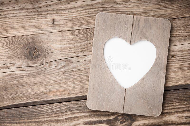 Hjärta formad ram på träbakgrund fotografering för bildbyråer