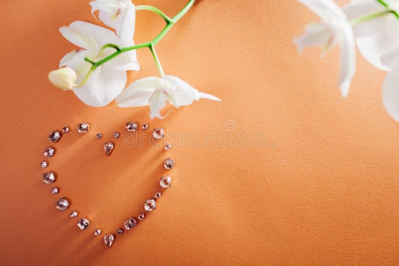 Hjärta formade ädelstenar med den vita orkidén Smycken som en gåva för valentin dag royaltyfri fotografi