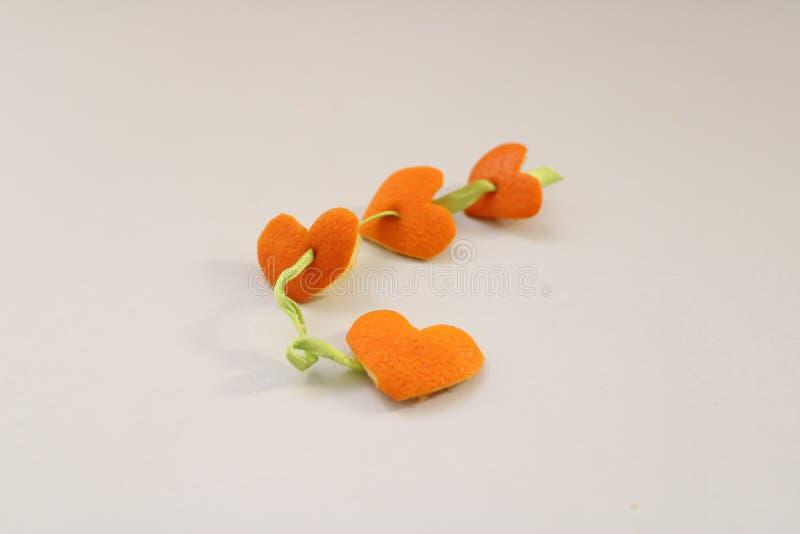 Hjärta-formade apelsinskal på den vita bakgrunden fotografering för bildbyråer